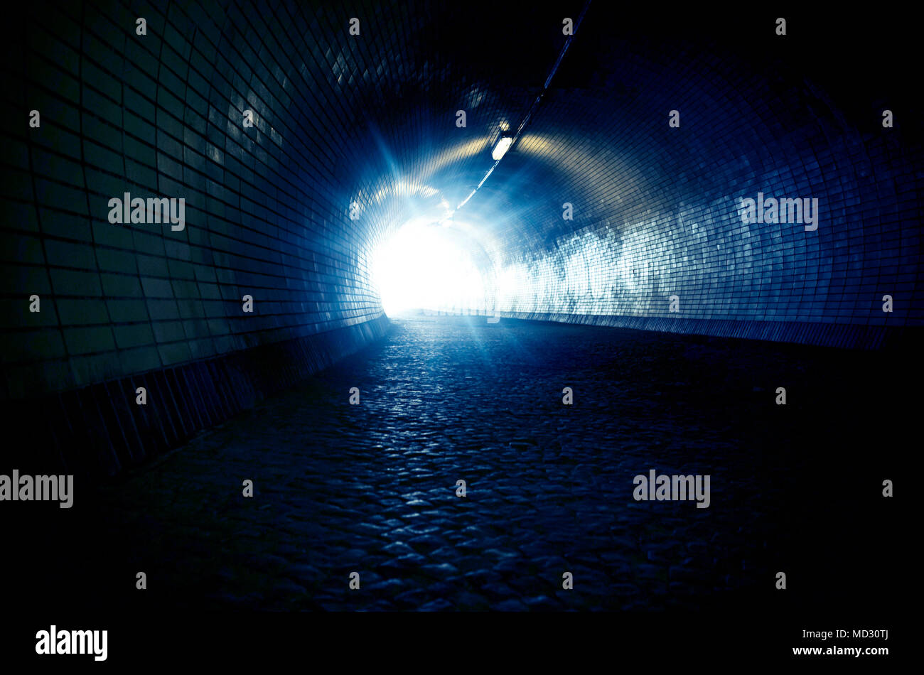 dark tunnel with light at the end of it - Stock Image