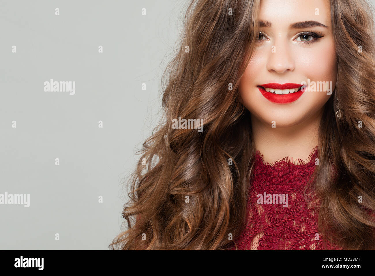 Young Woman with Long Healthy Permed Hair. Portrait of Cute Smiling Girl Fashion Model with Red Lips Makeup Stock Photo