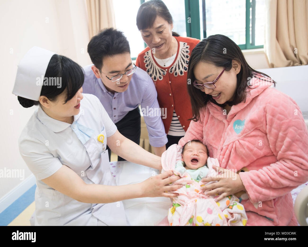 Wuhan, China's Hubei Province. 18th Apr, 2018. A medical worker (1st L, front) directs a new mother to take care of her baby at a maternity ward in Wuhan Women and Children Medical Care Center in Wuhan, capital of central China's Hubei Province, April 18, 2018. A total of 17 new maternity wards opened here recently to offer comprehensive medical service in labor, delivery, recovery and postpartum phases. New mothers, accompanied by their families, can receive the medical treatment at these separate wards before and after giving birth. Credit: Xiong Qi/Xinhua/Alamy Live News - Stock Image