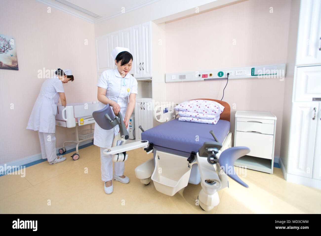 Wuhan, China's Hubei Province. 18th Apr, 2018. Medical workers settle facilities at a maternity ward in Wuhan Women and Children Medical Care Center in Wuhan, capital of central China's Hubei Province, April 18, 2018. A total of 17 new maternity wards opened here recently to offer comprehensive medical service in labor, delivery, recovery and postpartum phases. New mothers, accompanied by their families, can receive the medical treatment at these separate wards before and after giving birth. Credit: Xiong Qi/Xinhua/Alamy Live News - Stock Image
