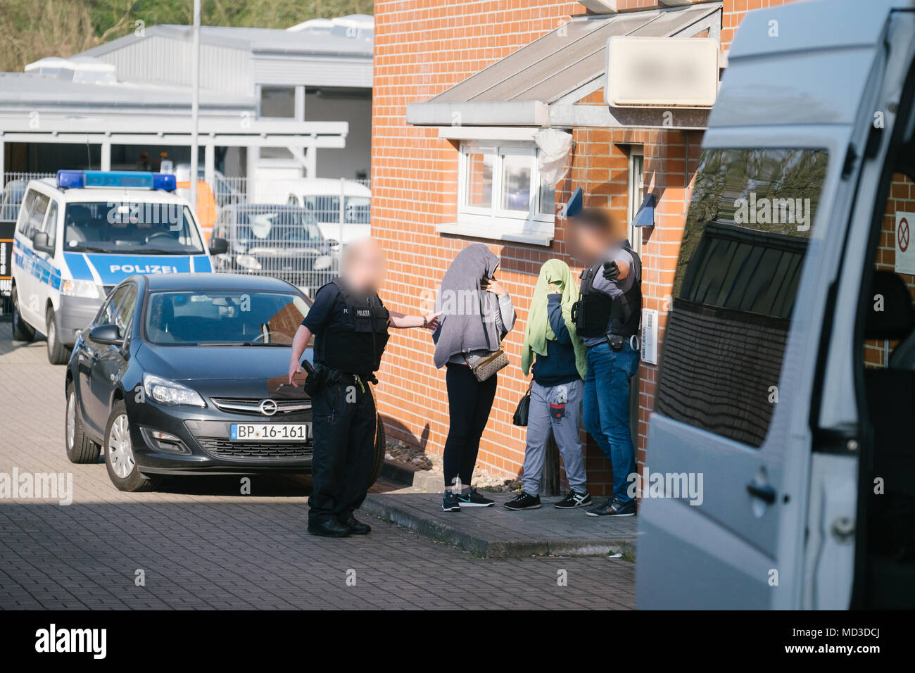 18 April 2018, Rastatt, Hanover: Police forces leading five women from a house in the district of Anderten. The police is cracking down on organized crime in a large-scale, nationwide raid starting Wednesday morning. According to the German police in Stuttgart, the focus lies on forged visas, human trafficking, pimping, and forced prostitution of Thai women. (Faces are blurred for legal reasons) Photo: Ole Spata/dpa Stock Photo