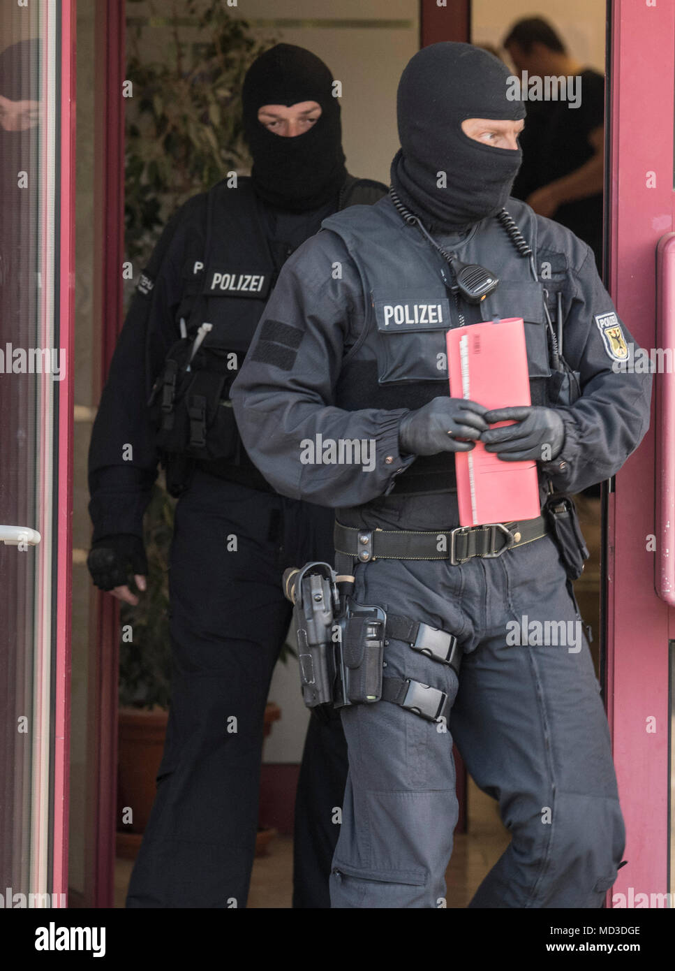 18 April 2018, Rastatt, Maintal: Masked officers of the German police force during a raid of a brothel. The police is cracking down on organized crime in a large-scale, nationwide raid starting Wednesday morning. According to the German police in Stuttgart, the focus lies on forged visas, human trafficking, pimping, and forced prostitution of Thai women. More than 1500 police officers are taking part in this raid. Photo: Boris Roessler/dpa Stock Photo