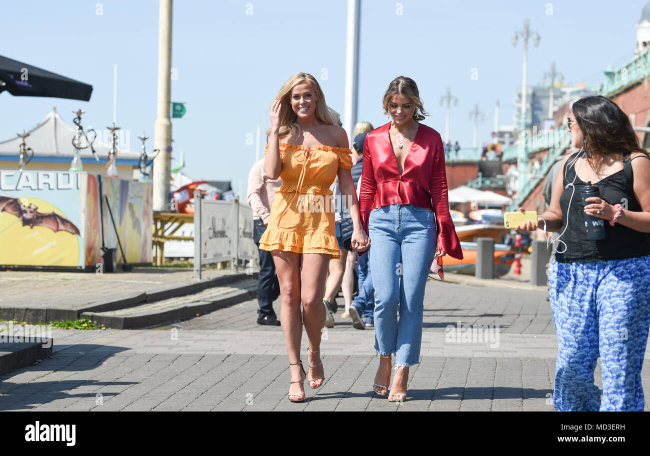 Brighton UK 18th April 2018  - Chloe Meadows (left) and Chloe Lewis two of the stars of the reality television show The Only Way is Essex enjoying a stroll along Brighton seafront as they film at the Shooshh Bar in hot sunshine today Credit: Simon Dack/Alamy Live News - Stock Image