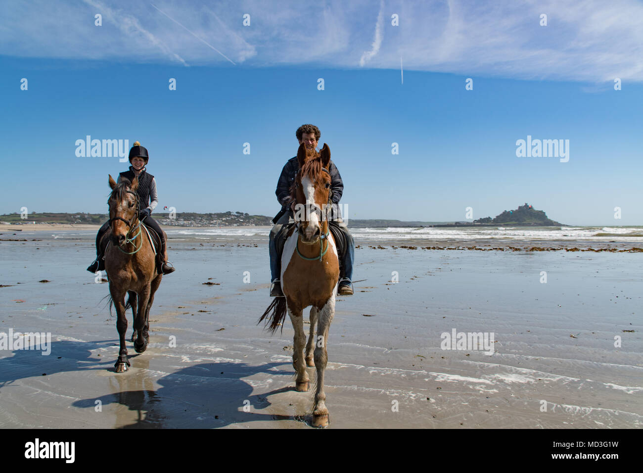 Longrock, near Marazion, Cornwall, UK. 18th April 2018. UK Weather. A stiff onshore breeze kept the temperatures down to 19 degrees C this lunchtime on the beach at Longrock. Cornwall swimming horses were out for a canter, however they won't be swimming until the sea warms up a bit more in May. Credit: Simon Maycock/Alamy Live News - Stock Image