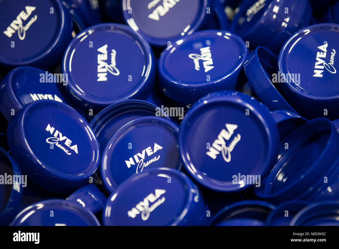 18 April 2018, Germany, Hamburg: Plastic lids for Nivea-Creme in a storage container at the production plant of the German personal-care company Beiersdorf. Photo: Christian Charisius/dpa - Stock Image