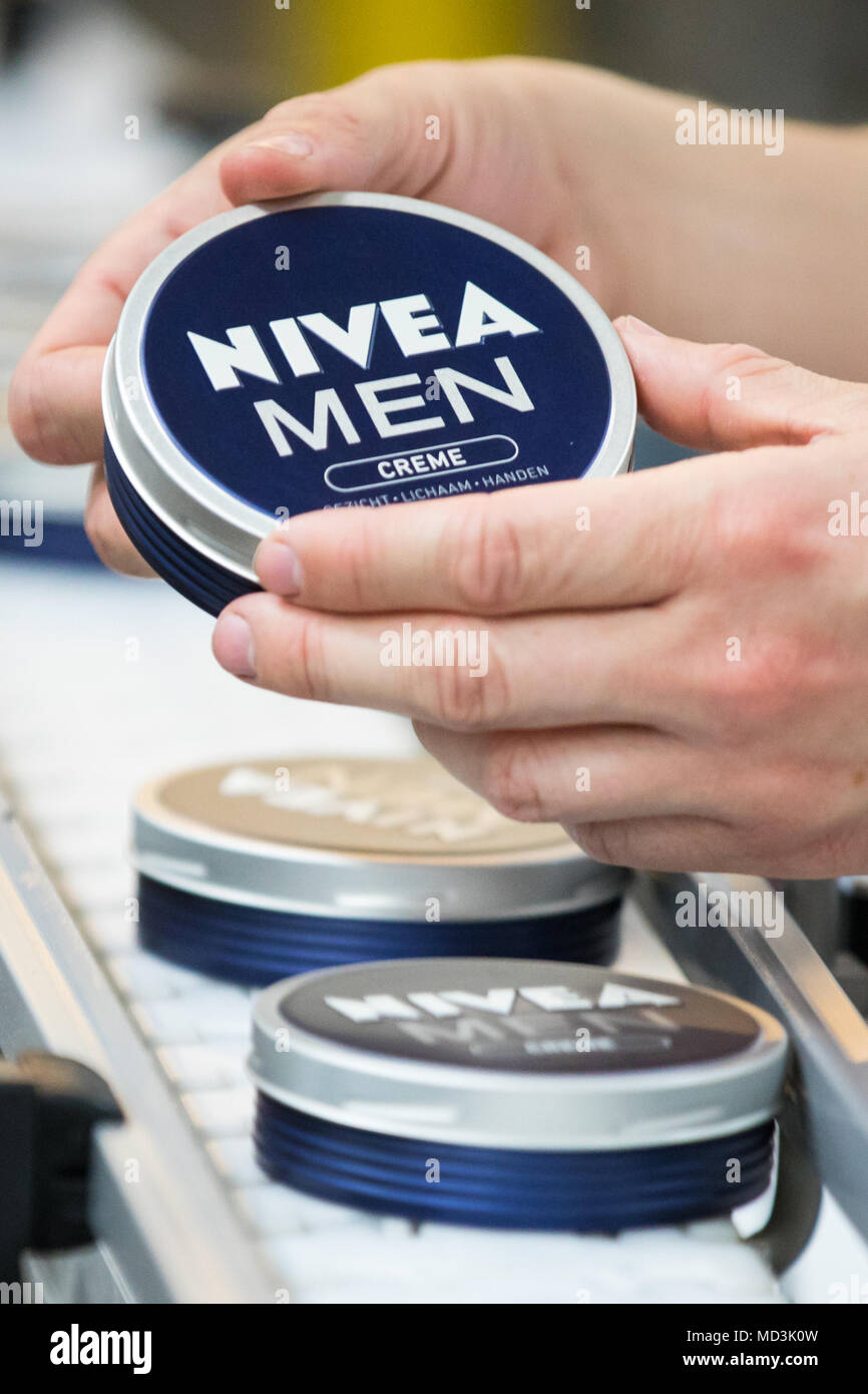 18 April 2018, Germany, Hamburg: An employee checks a Nivea-Creme of 'Nivea Men' at the production plant of the German personal-care company Beiersdorf. Photo: Christian Charisius/dpa - Stock Image