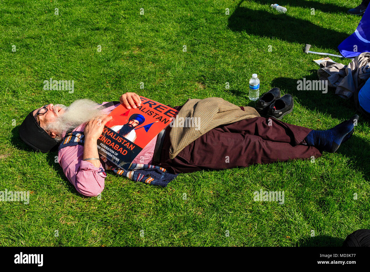 London, UK. 18th April 2018. A Sikh demonstrator rests in parliament Square after protesting against Indian Prime Minister Modi's visit to London, Parliament Square, London, Uk. Credit: Grant Rooney/Alamy Live News - Stock Image