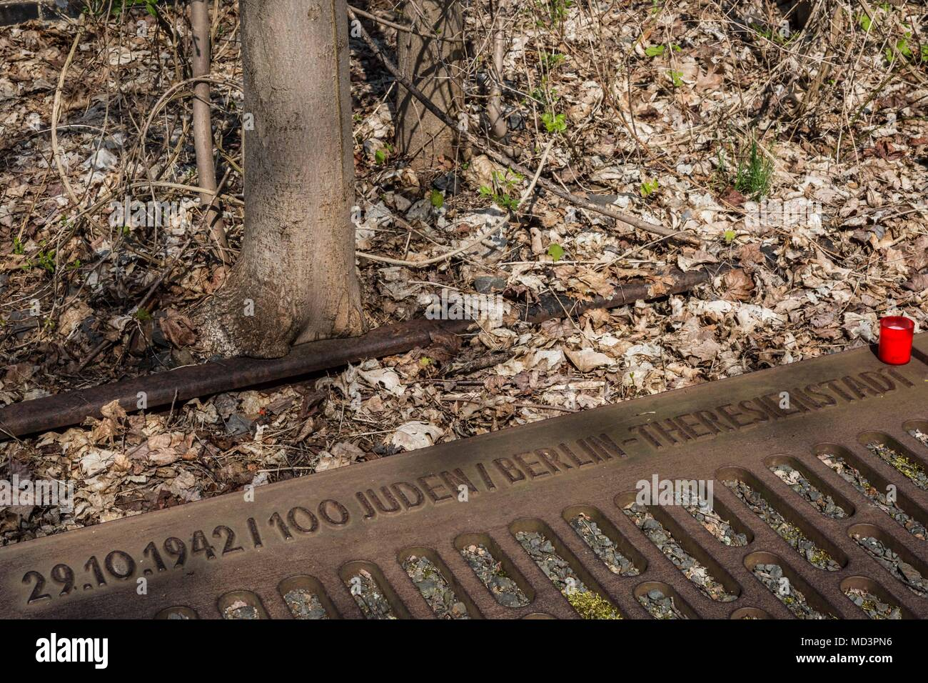 Berlin, Germany. 18th Apr, 2018. Wednesday, April 18, 2018.An unlit candle is placed on a plaque at the Gleis 17 (Track 17) Memorial at Grunewald Station in Berlin, Germany. Track 17 at the Grunewald Station was one of the major sites of deportation of the Berlin Jews during World War II. Prior to 1942, the trains from this site left mainly for the ghettos of Litzmannstadt and Warsaw. But from 1942, the trains went directly to concentration camps including Auschwitz and Thereisienstadt.Plaques with details of every deportation shipment of Jews from Berlin exist on both sides of the platf - Stock Image