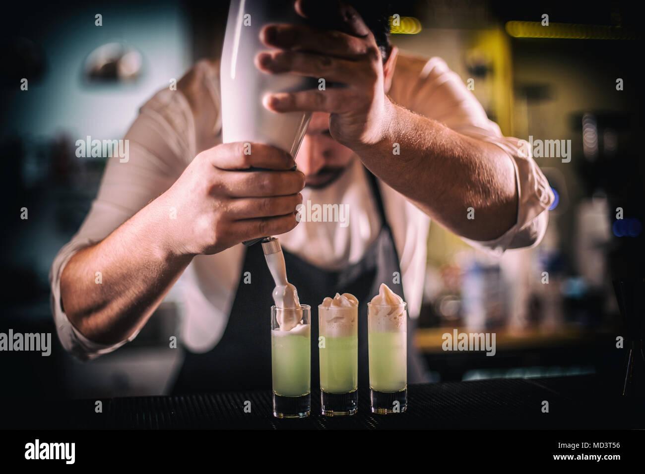 Bartender decorating shots with hazelnut whipped cream - Stock Image