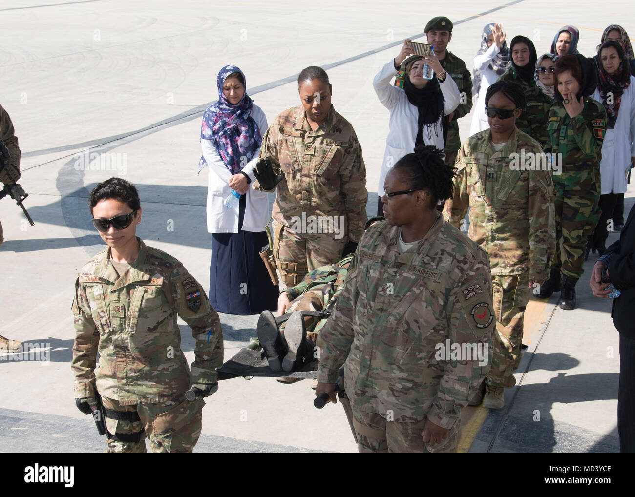 Master Sgt. Ruth Celestine, Train, Advise, Assist Command-Air medical advisor, discusses how to transition from a four-person litter carry to a two-person carry during an orientation class March 3, 2018, Kabul Air Wing, Afghanistan. The orientation was setup to help many of the new medics understand C-130 patient litter capabilities, casualty evacuation pre-flight mission configurations and in-flight/post-flight patient care requirements. (U.S. Air Force photo by Staff Sgt. Jared J. Duhon) - Stock Image