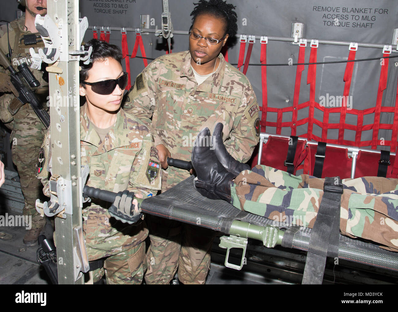 Tech Sgt. Kimberly Olivier, Train, Advise, Assist Command-Air airfield management advisor, Master Sgt. Jennifer Louverture  TAAC-Air plans, scheduling and documenting advisor, demonstrates how to lock the patient litter into place on C-130s March 3, 2018, Kabul Air Wing, Afghanistan. In total five TAAC- Air advisors, including Master Sgt. Ruth Celestine, Train, Advise, Assist Command-Air medical advisor, informed the Afghan women medics about pre-flight, in-flight and post-flight patient care requirements for the C-130. (U.S. Air Force photo by Staff Sgt. Jared J. Duhon) - Stock Image