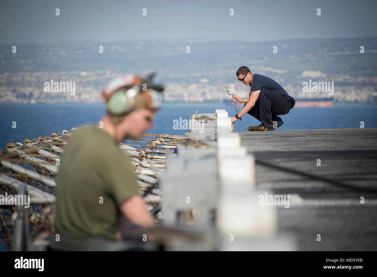180319-N-QJ850-0023 LIMASSOL, Cyprus (March 19, 2018) A Sailor and Marine do maintenance on the flight deck as the Wasp-class amphibious assault ship USS Iwo Jima (LHD 7) arrives in Limassol, Cyprus, for a scheduled port visit March 19, 2018. Iwo Jima, homeported in Mayport, Florida, is in Limassol, Cyprus, as part of a scheduled port visit as the ship conducts naval operations in the U.S. 6th Fleet area of operations. (U.S. Navy photo by Mass Communication Specialist 2nd Class Andrew Murray/Released) - Stock Image
