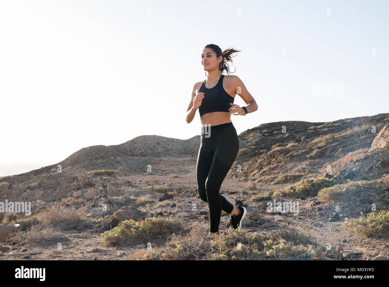 Young female runner running on dirt track in arid landscape, Las Palmas, Canary Islands, Spain - Stock Image