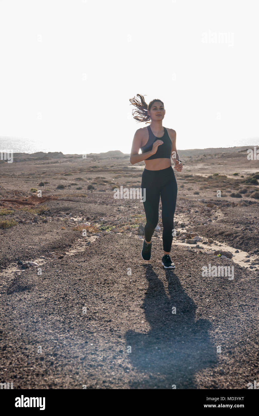Young female runner running in arid coastal landscape, Las Palmas, Canary Islands, Spain - Stock Image