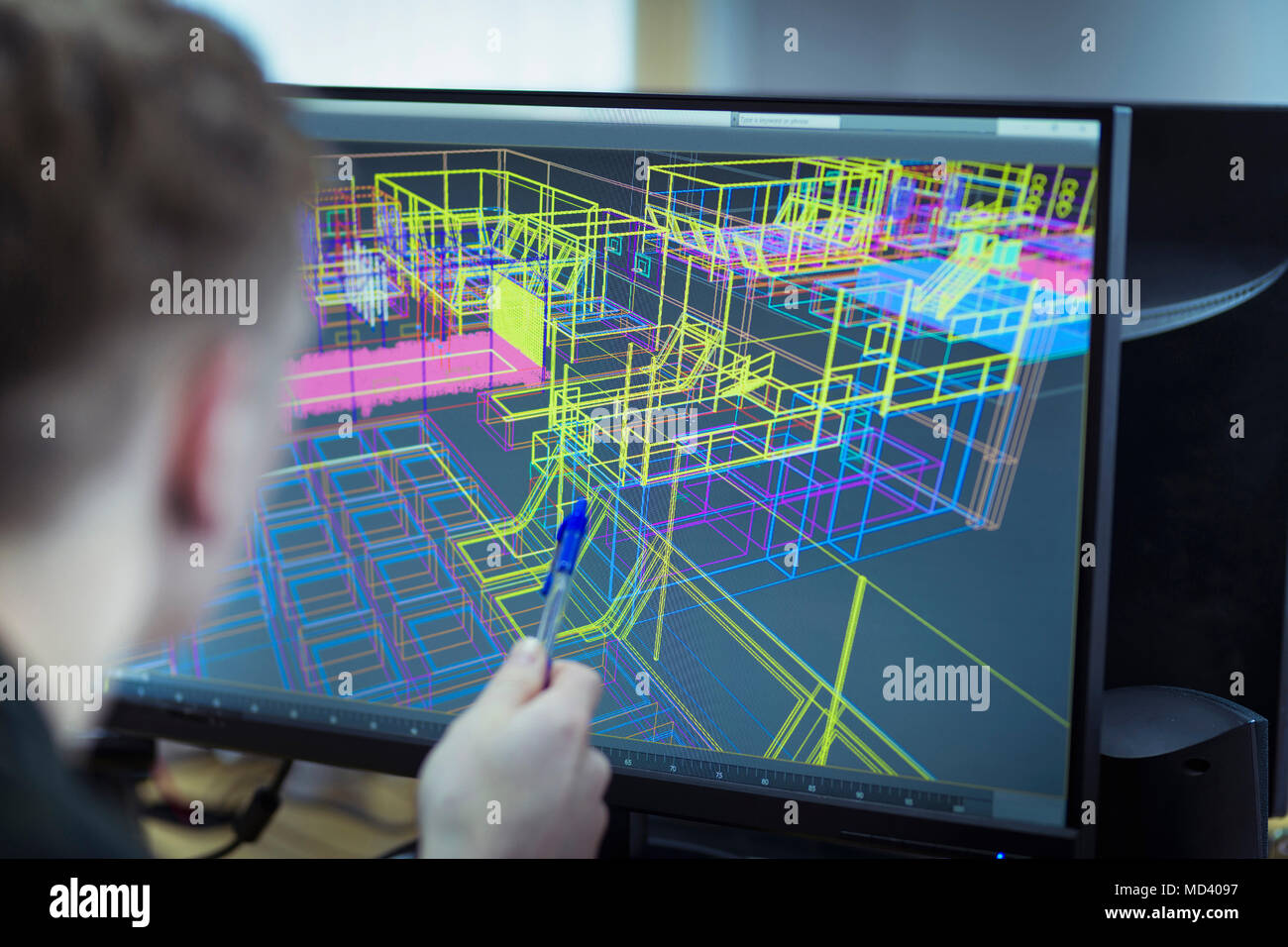 Worker looking at CAD wireframe industrial design on screen - Stock Image