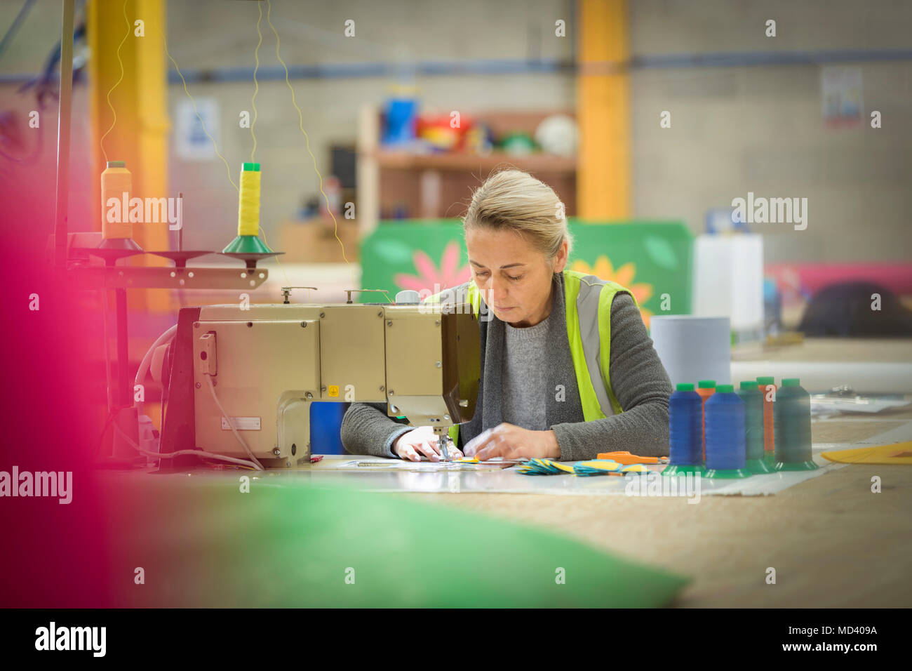 Female worker making cushions with sewing machine in factory - Stock Image