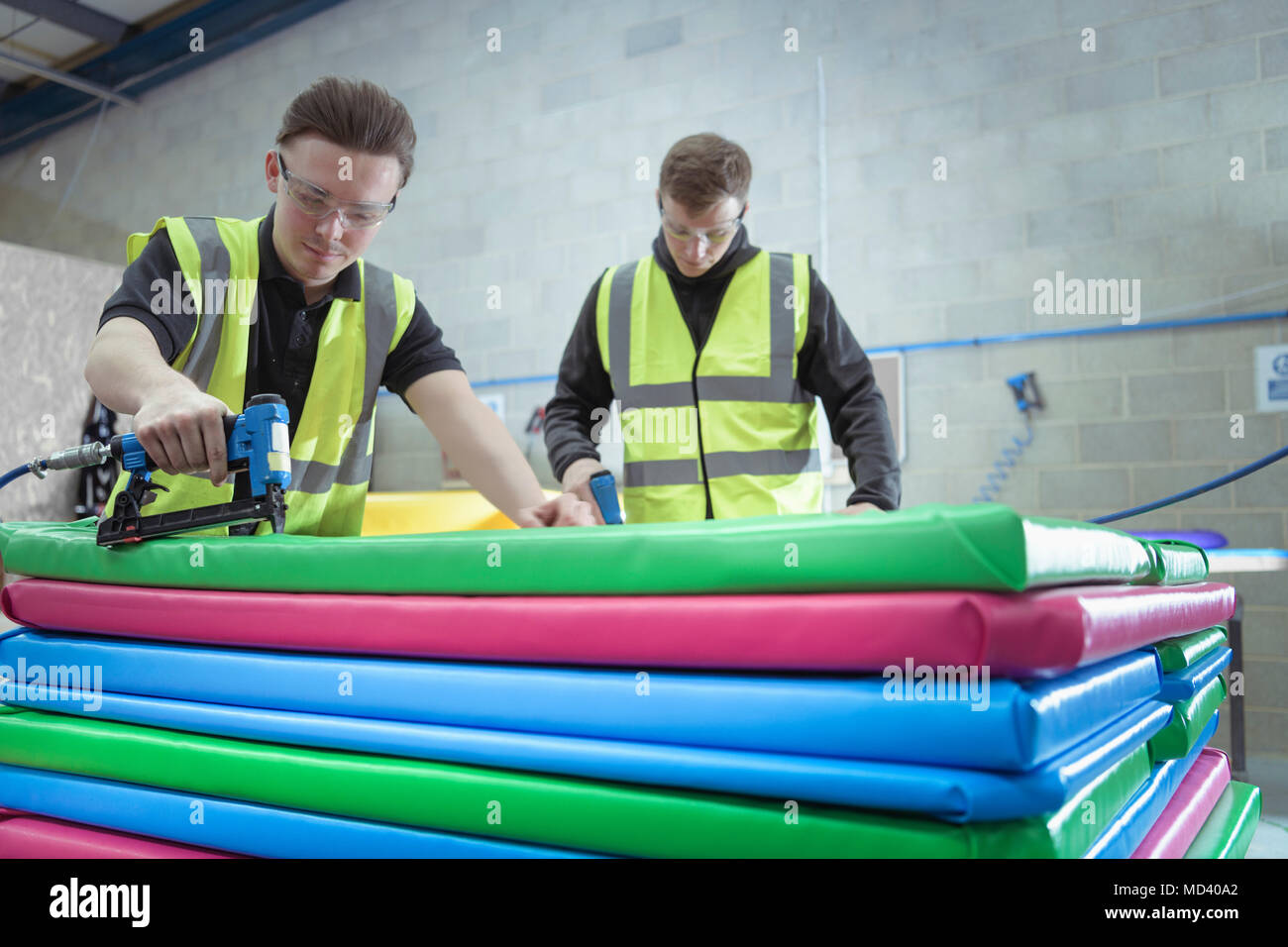 Workers assembling soft coloured mats in factory - Stock Image
