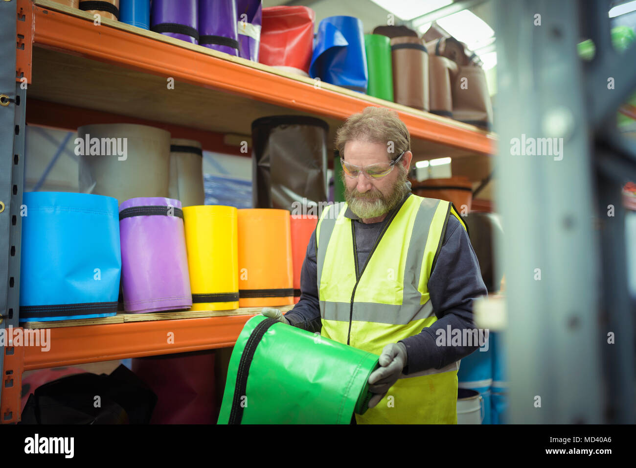 Worker selecting coloured vinyl rolls in factory - Stock Image