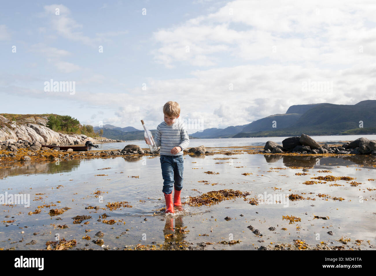 Boy with message in a bottle, Aure, More og Romsdal, Norway - Stock Image