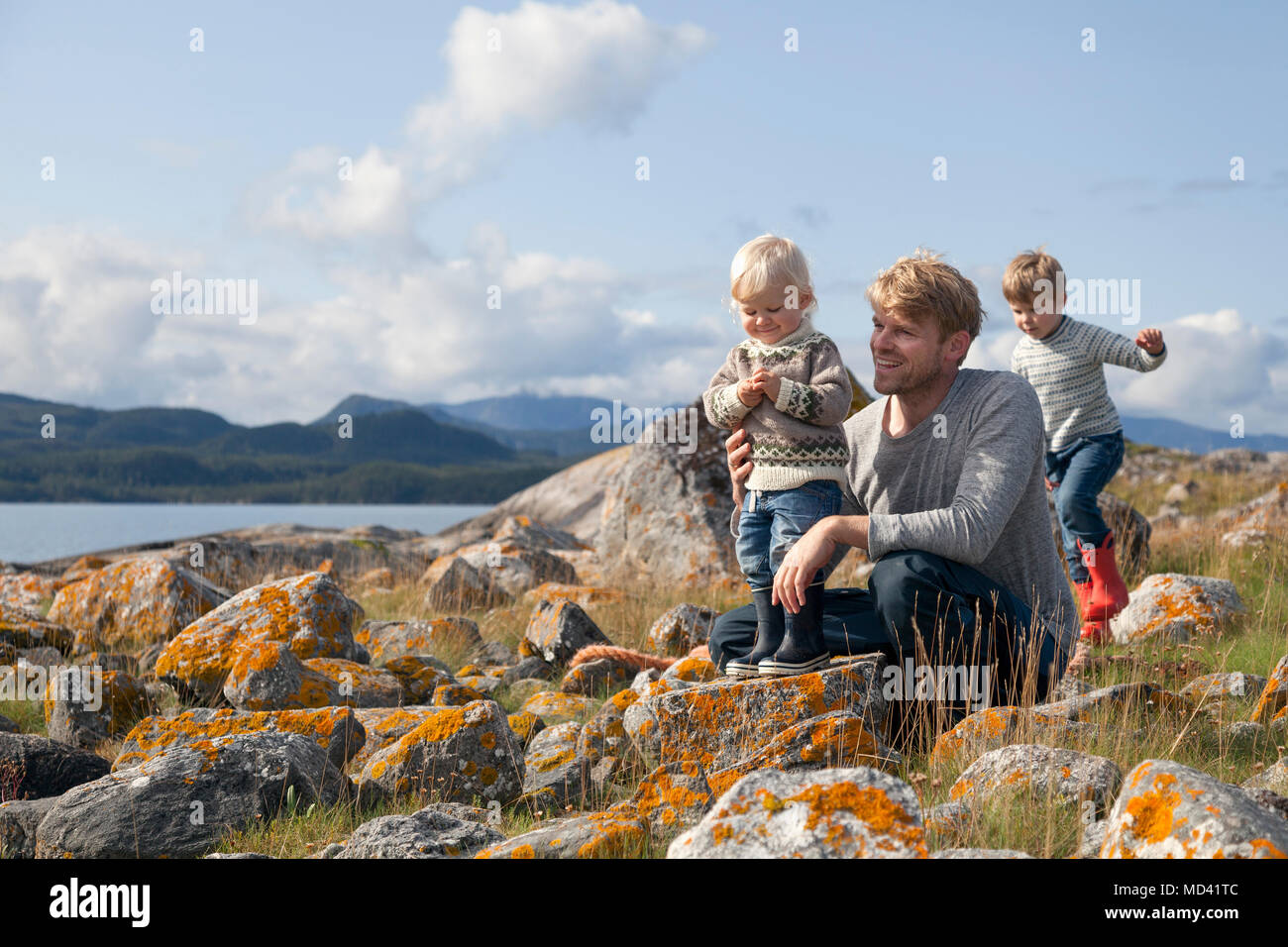 Man with sons playing by fjord, Aure, More og Romsdal, Norway - Stock Image