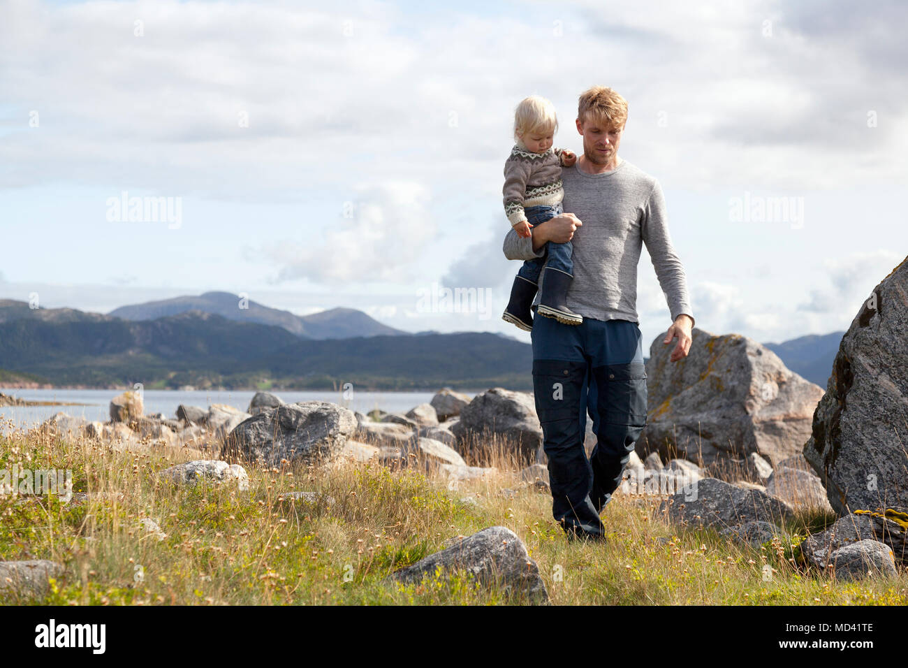 Man carrying son by fjord, Aure, More og Romsdal, Norway - Stock Image