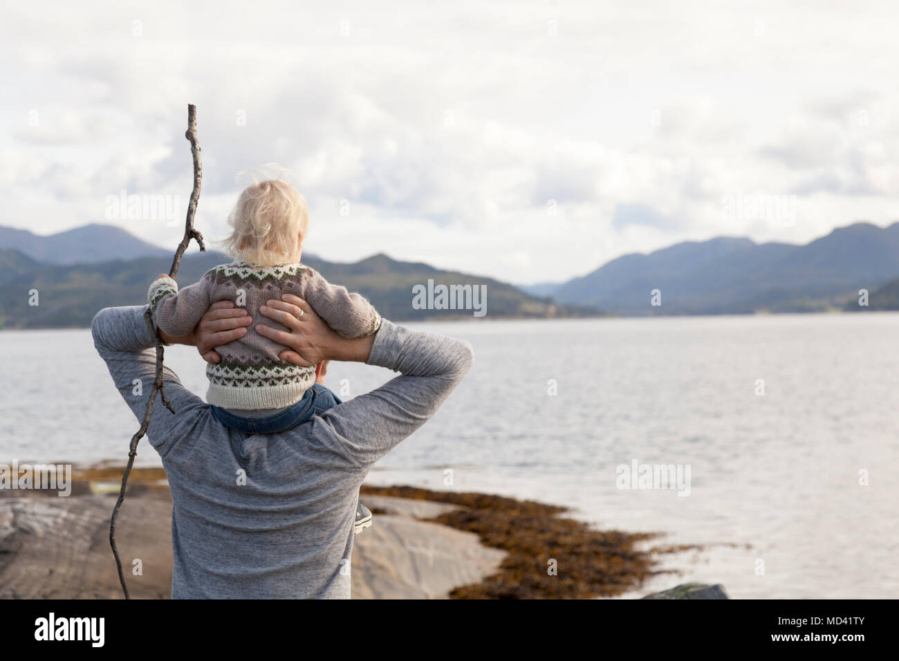 Man and son looking out at fjord, Aure, More og Romsdal, Norway - Stock Image