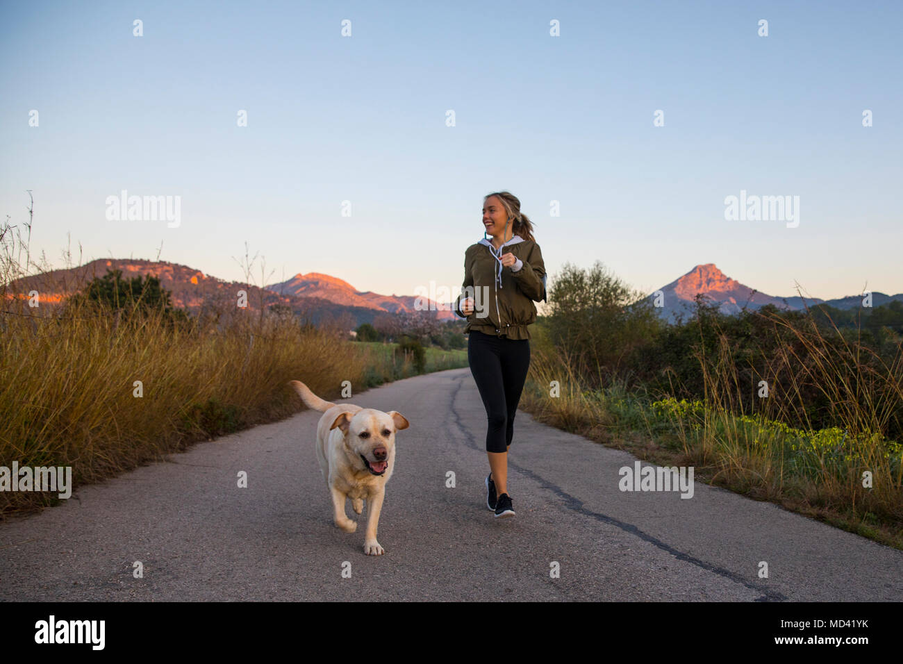 Young woman running along rural road with pet dog - Stock Image