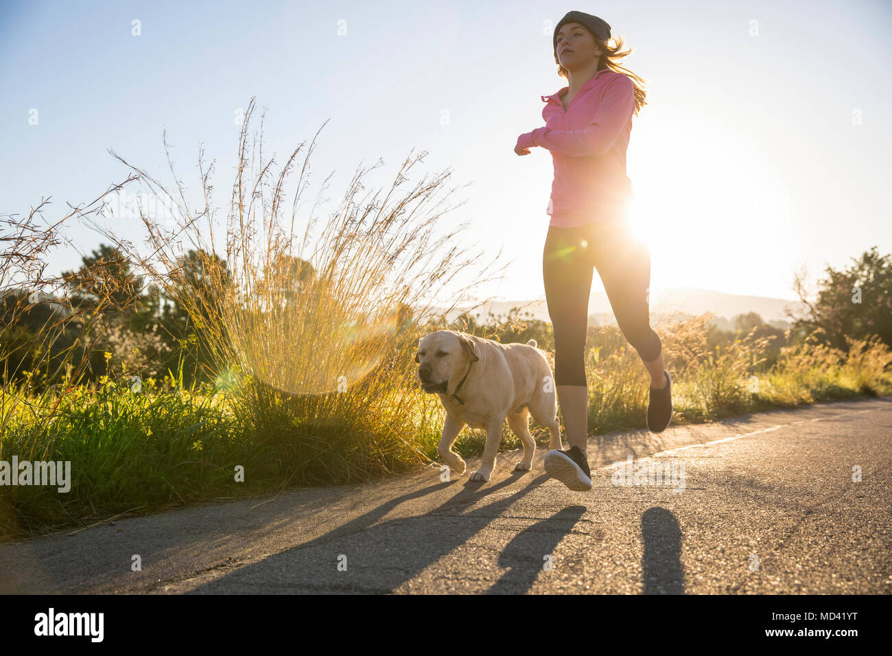 Young woman running along rural road with pet dog, low angle view - Stock Image