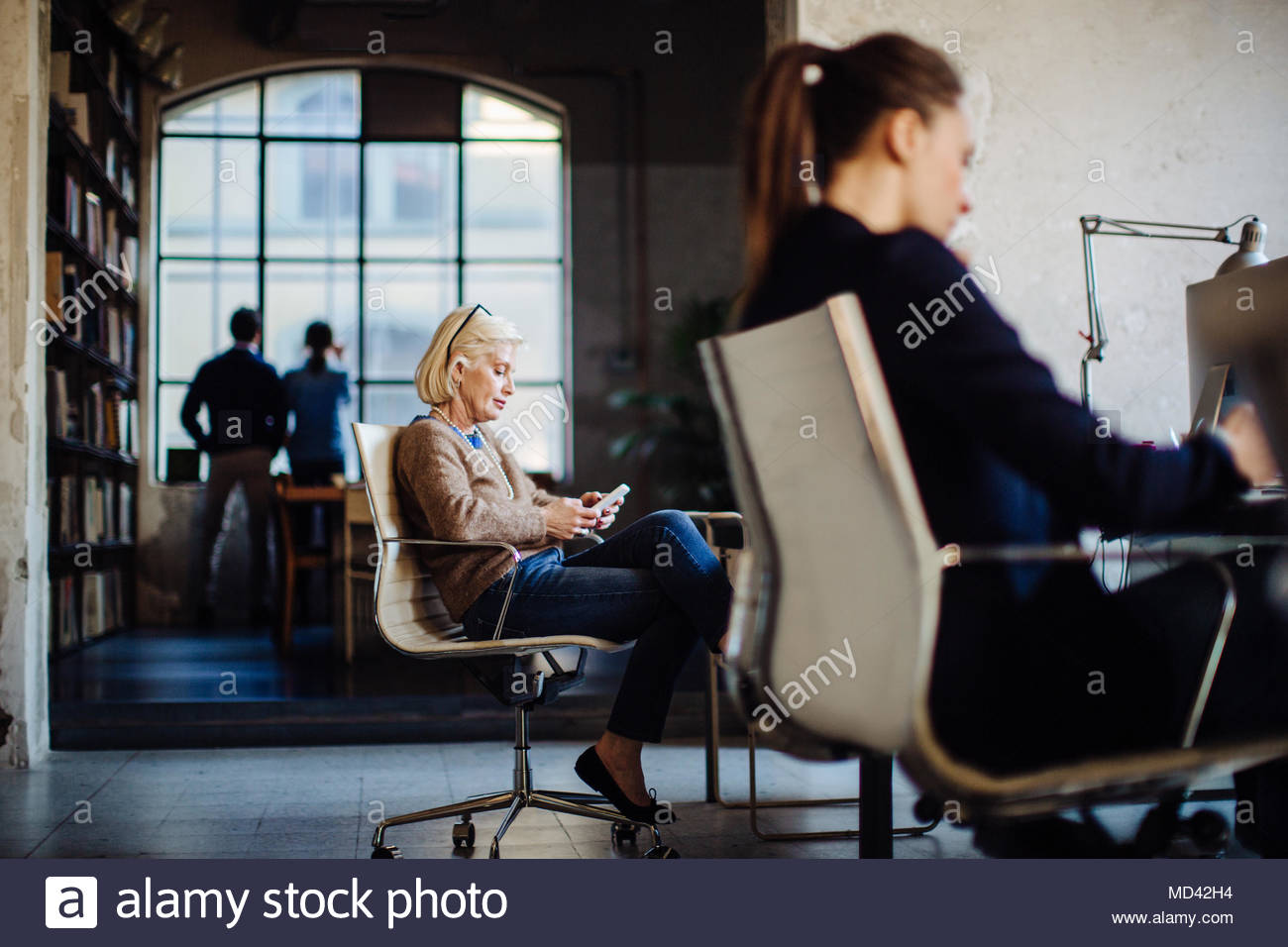 Businesspeople in office, two women sitting at desk working, businessman and woman looking out of window in background - Stock Image