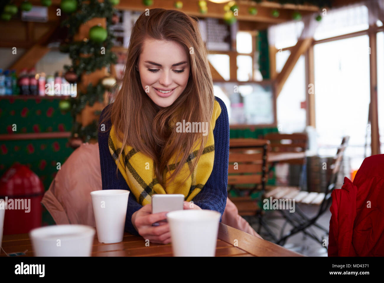Young woman smiling over text message on mobile phone - Stock Image