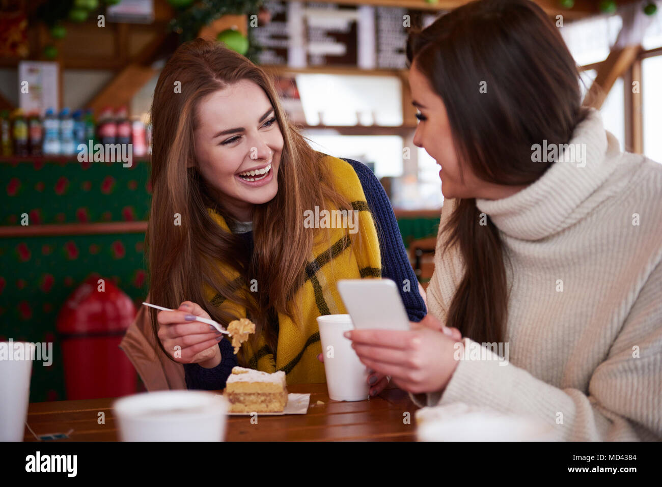 Young women smiling over text message on mobile phone - Stock Image