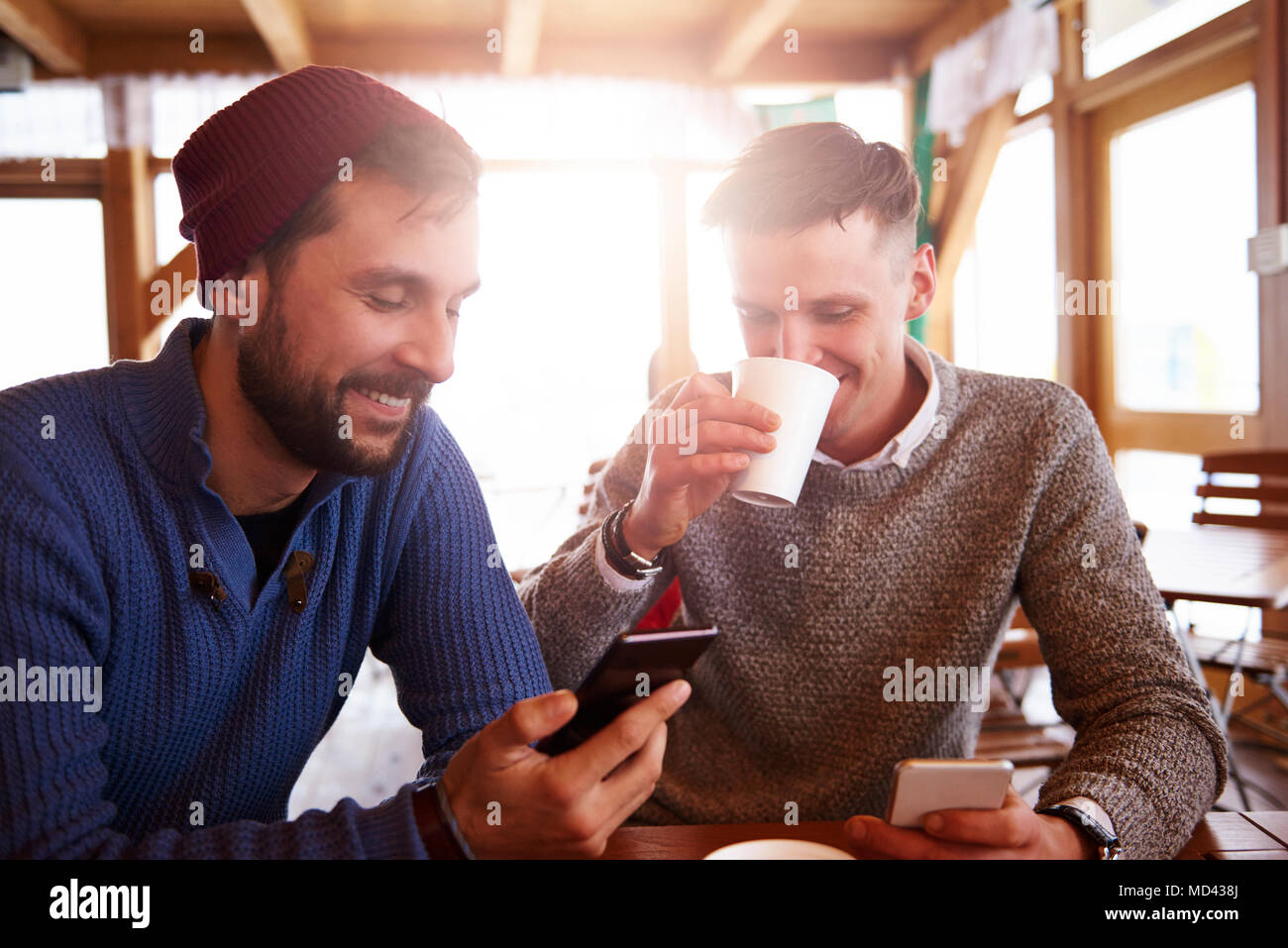 Young men smiling over text message on mobile phones Stock Photo