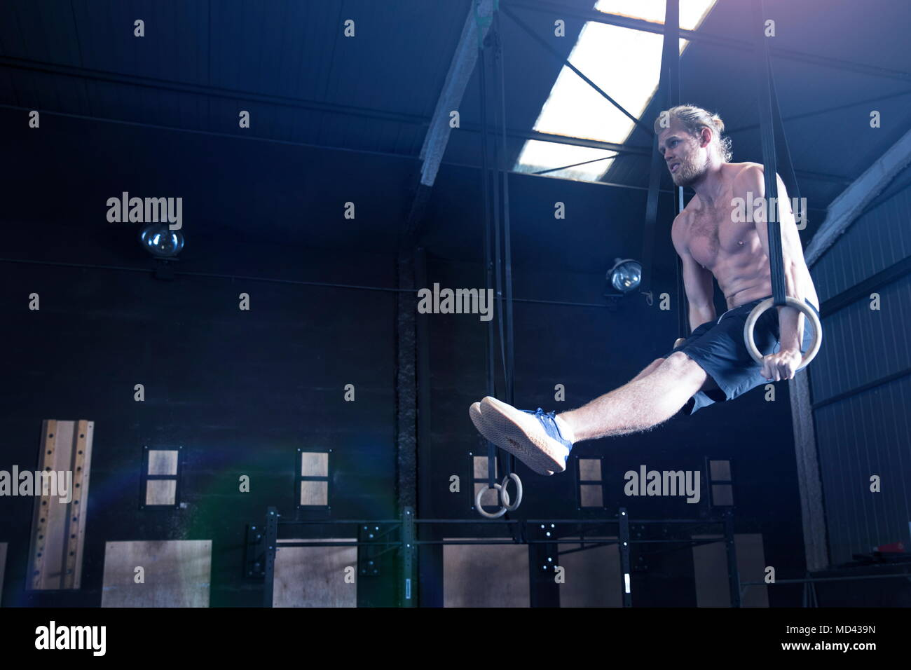 Man in gymnasium, balancing on gymnastic rings - Stock Image