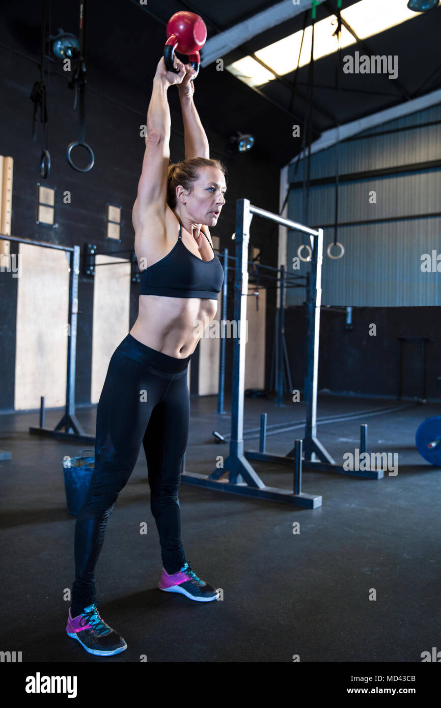 Woman exercising in gymnasium, using kettlebell - Stock Image
