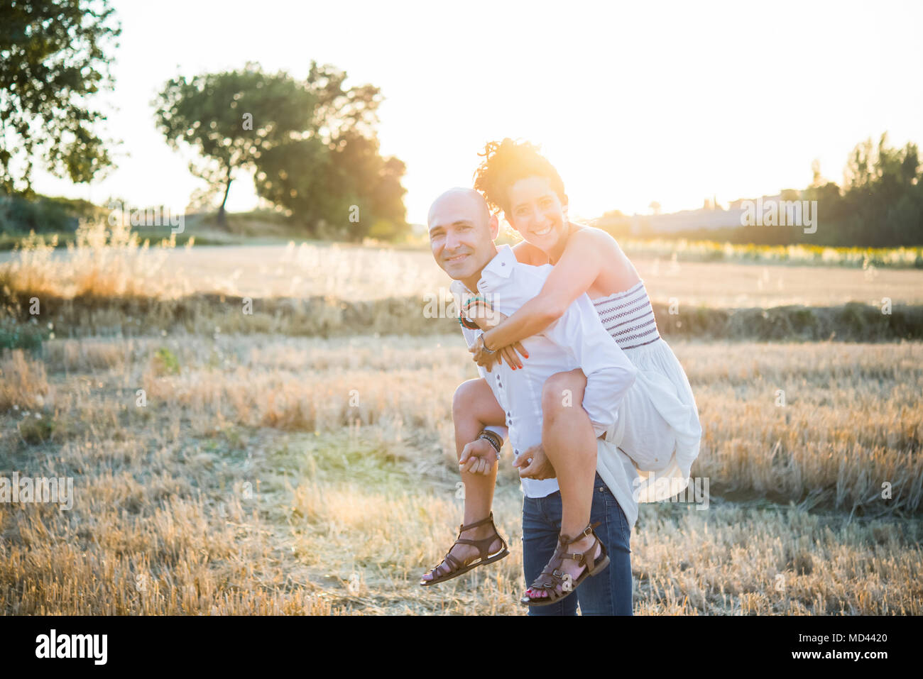 Portrait of heterosexual couple in field, man carrying woman on back - Stock Image