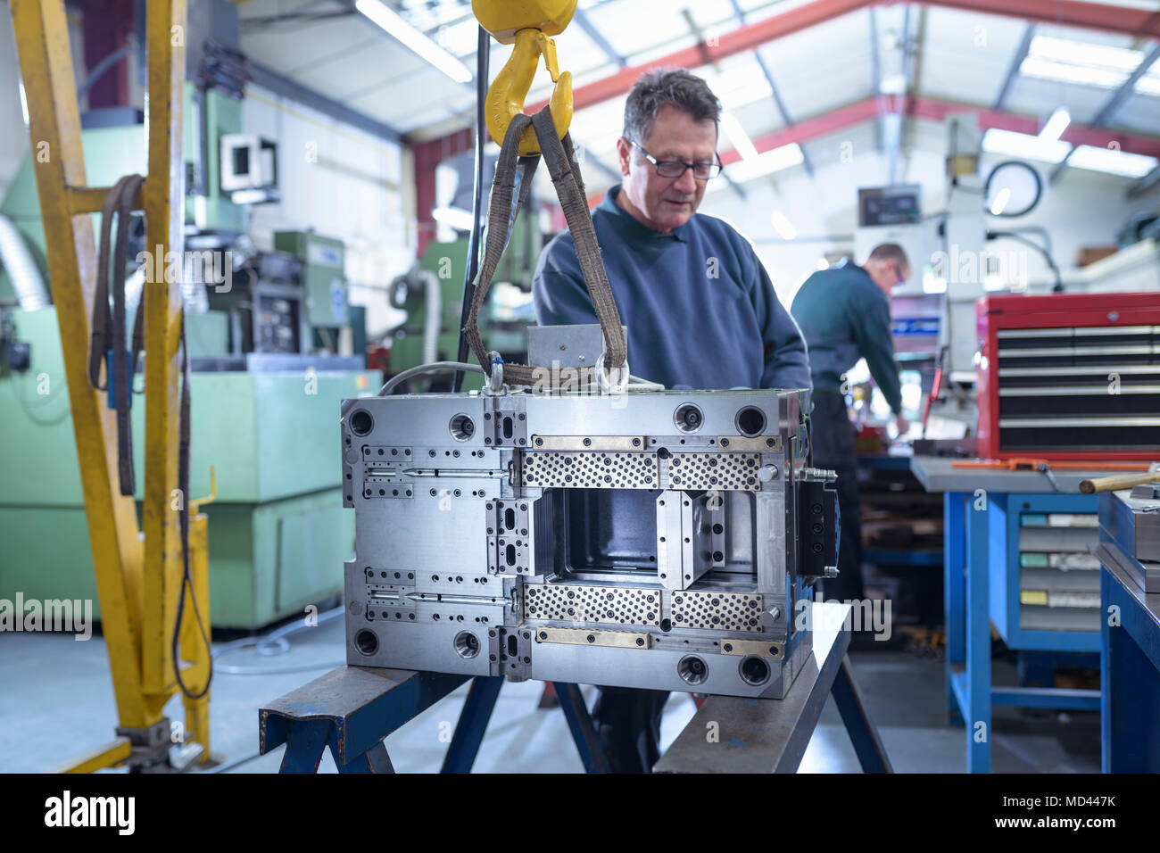 Engineer working on mould for plastic injection in precision engineering factory - Stock Image