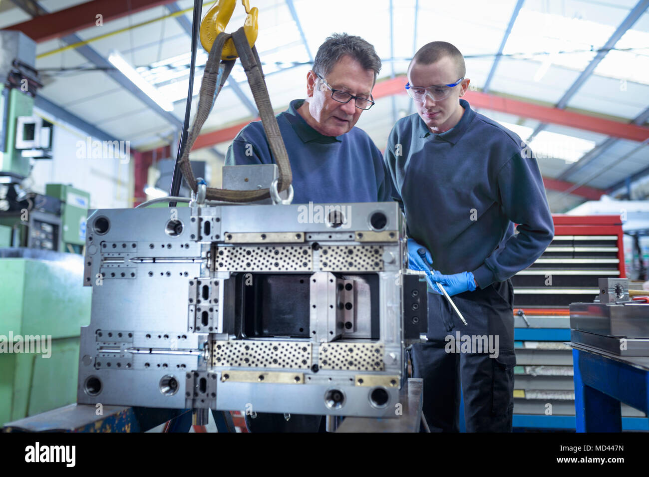 Engineer and apprentice working on mould for plastic injection in precision engineering factory - Stock Image