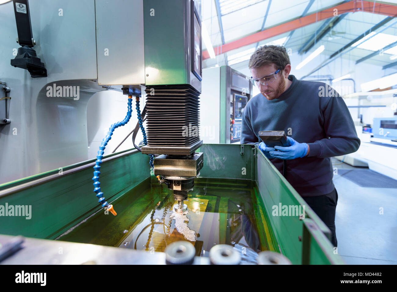 Engineer operating solid EDM (Spark Erosion Machine) in precision engineering factory - Stock Image