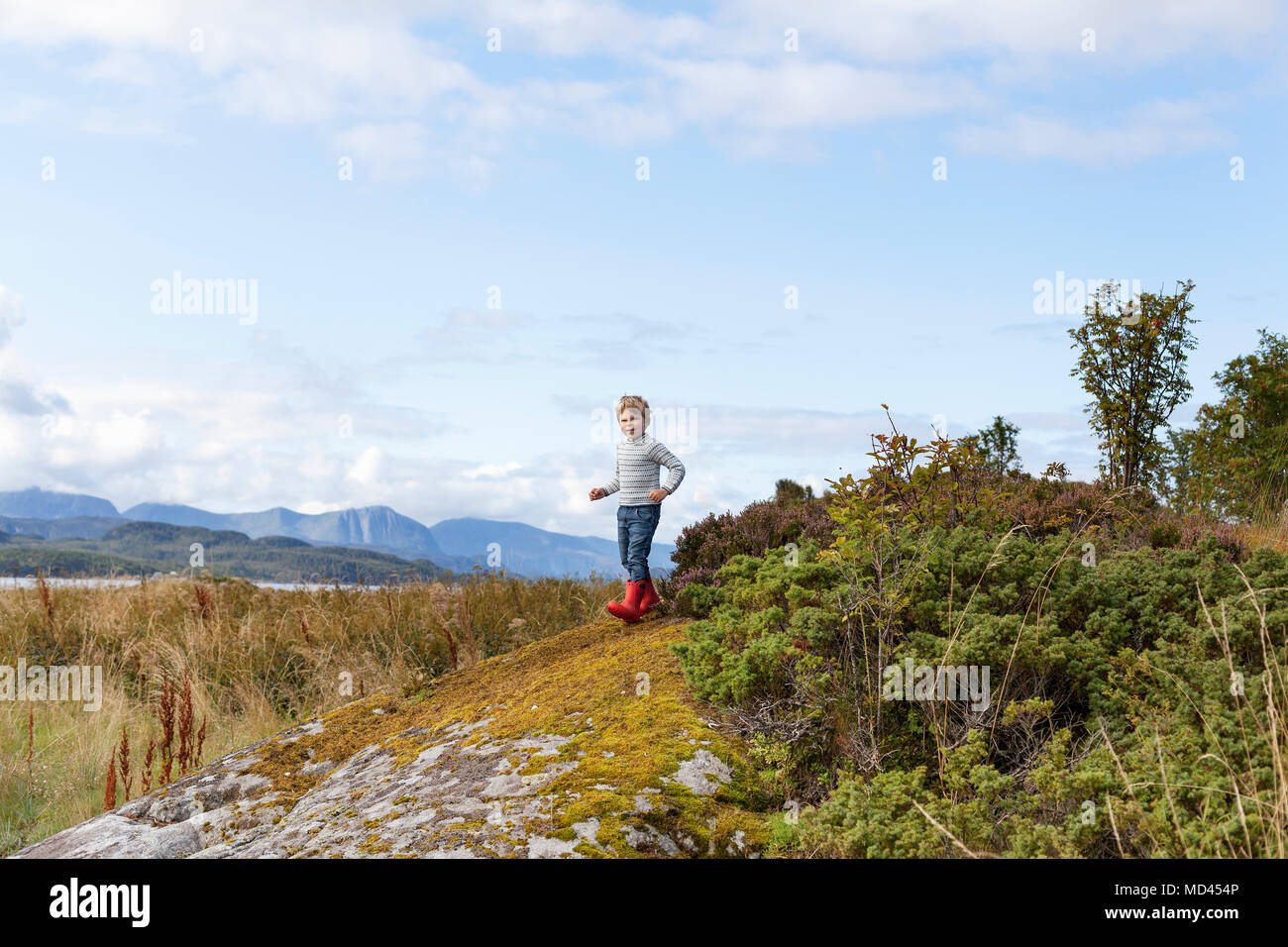 Boy playing on rock near fjord, Aure, More og Romsdal, Norway - Stock Image