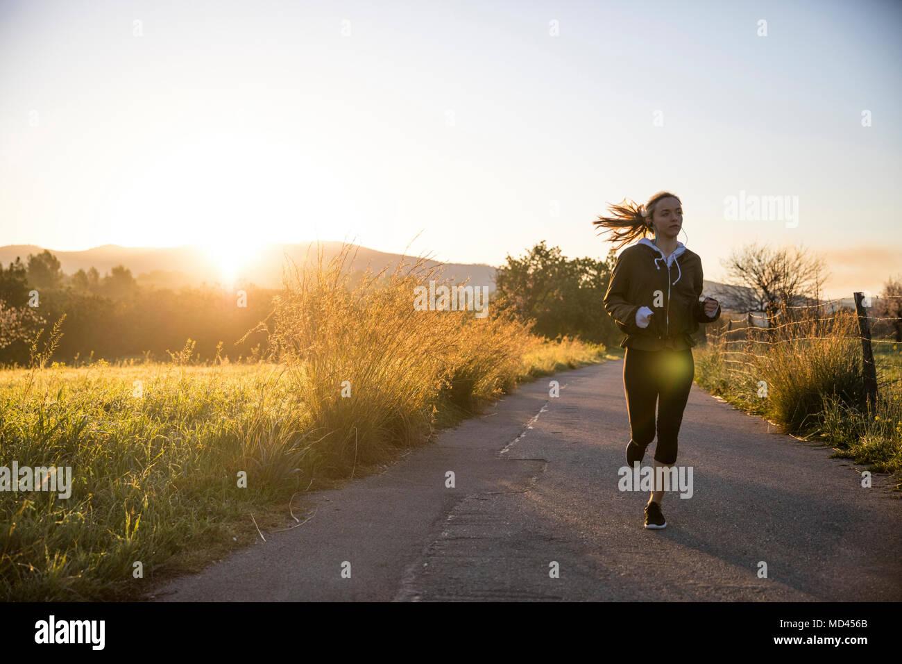 Young woman running along rural road - Stock Image