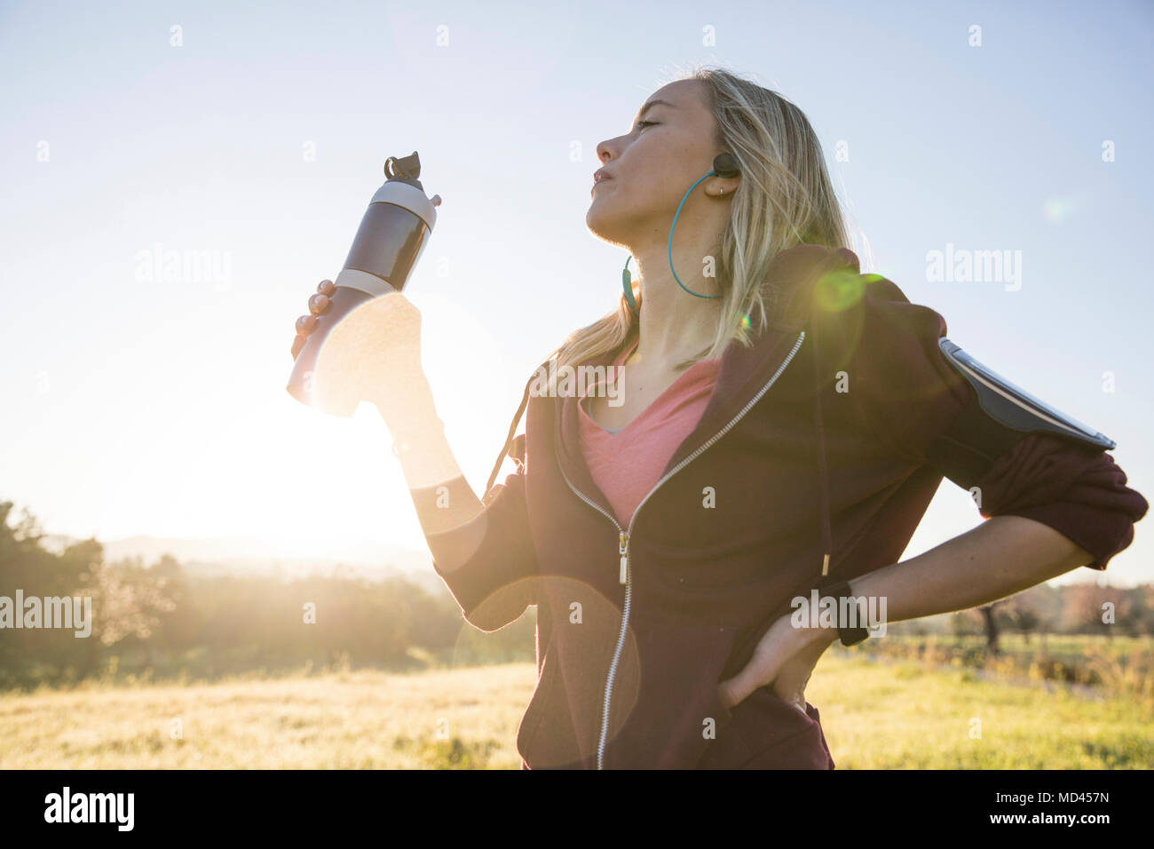 Young woman exercising outdoors, holding water bottle - Stock Image