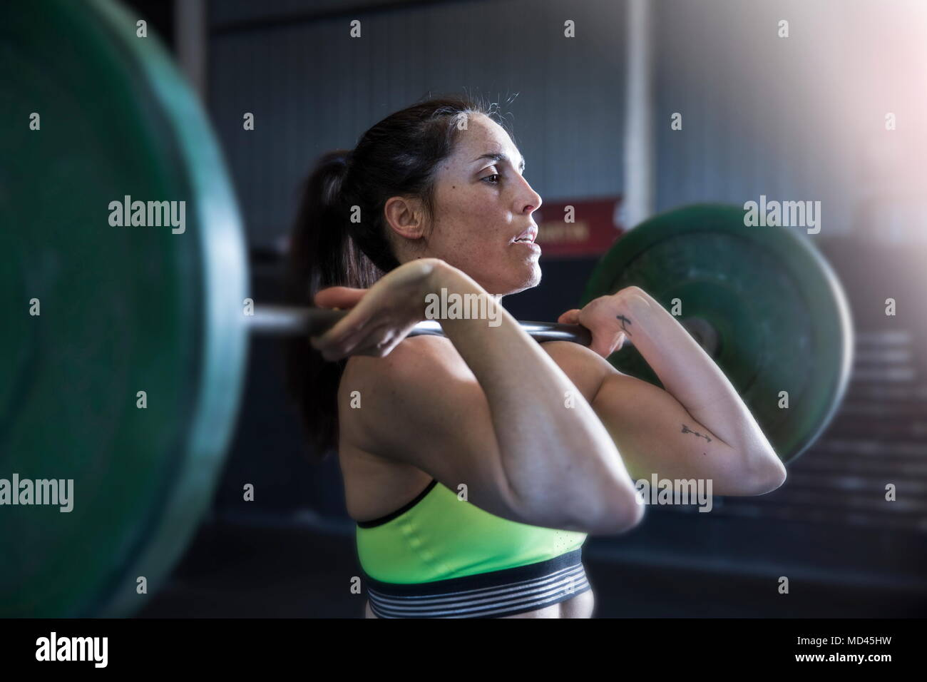 Woman exercising in gym, using barbell - Stock Image