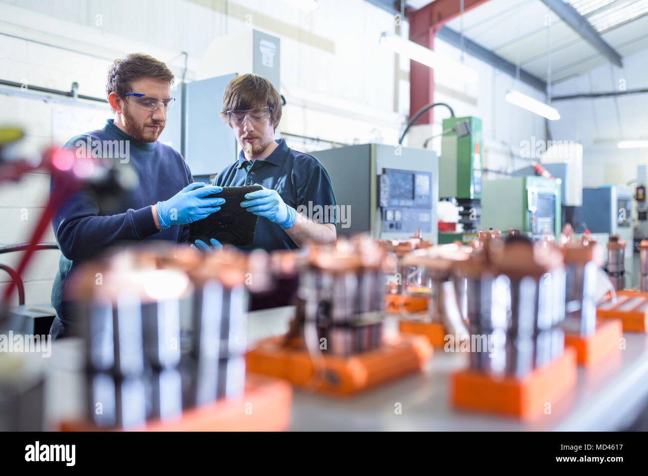 Engineers working with electrodes for electrical discharge machine in precision engineering factory - Stock Image