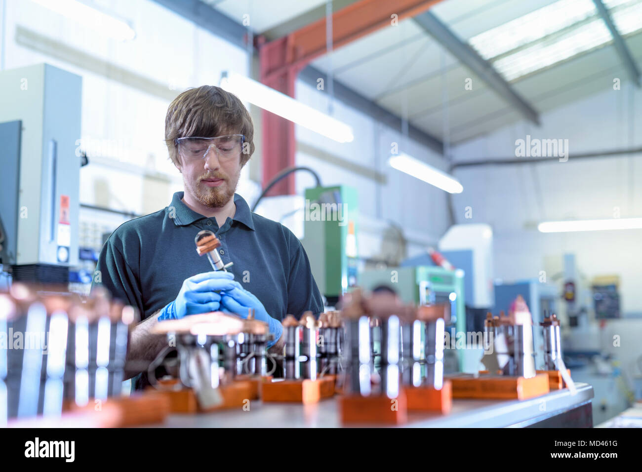 Engineer working with electrodes for electrical discharge machine in precision engineering factory - Stock Image