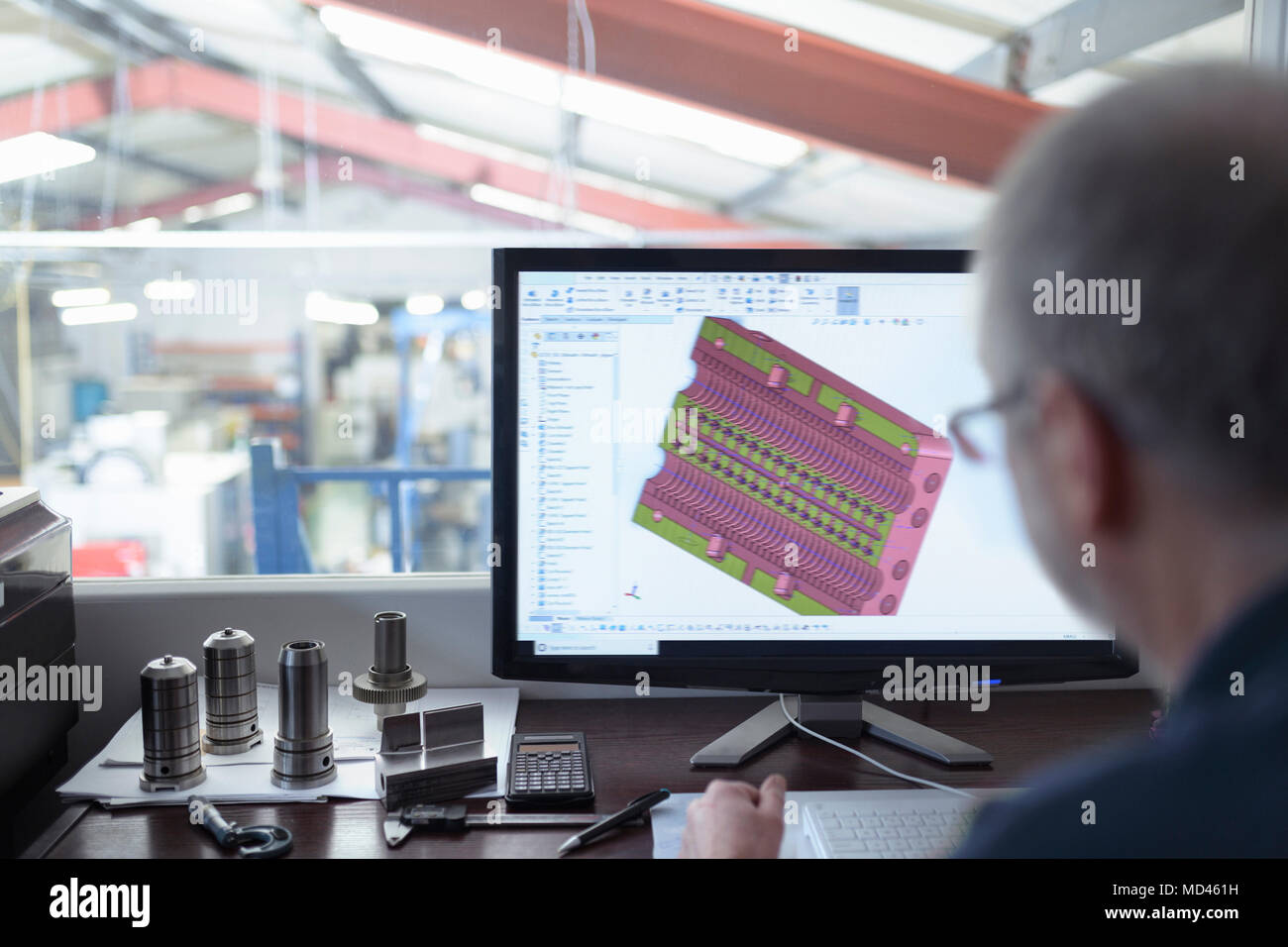 Engineer using CAD program in precision engineering factory - Stock Image