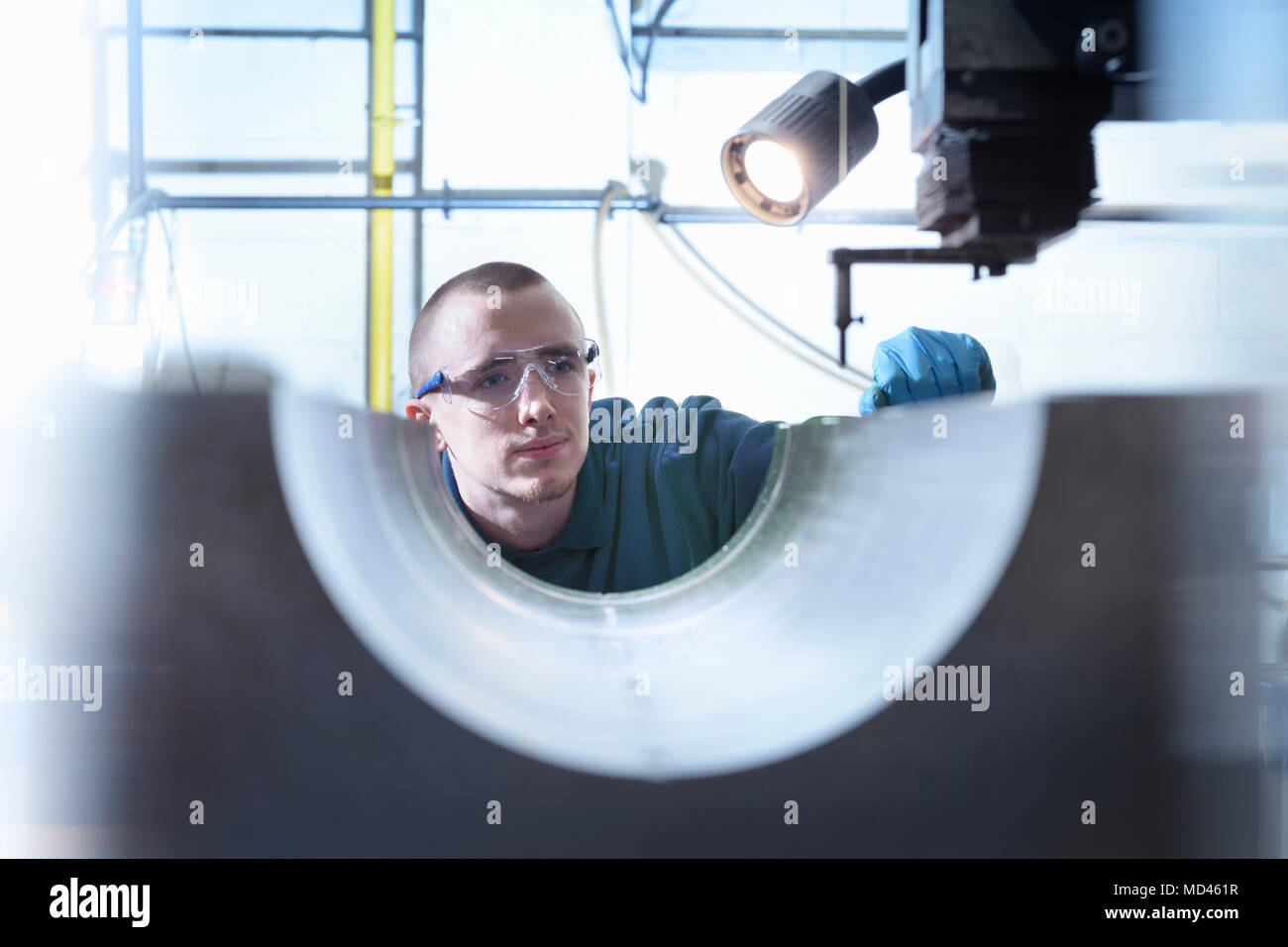 Engineer using electrical discharge (EDM) to drill holes in metal in precision engineering factory - Stock Image