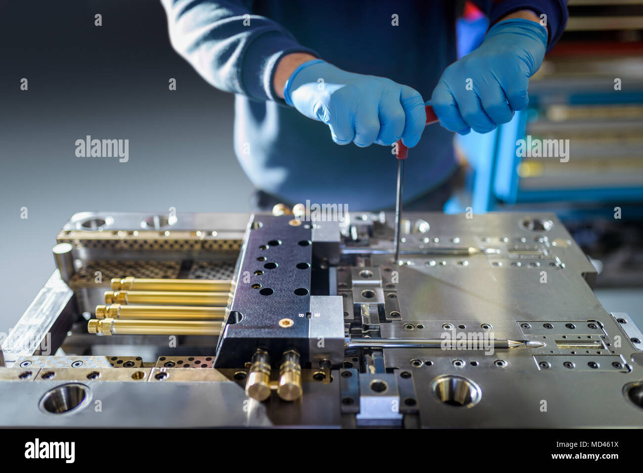 Engineer working on plastic injection mould in precision engineering factory, mid section, close up - Stock Image