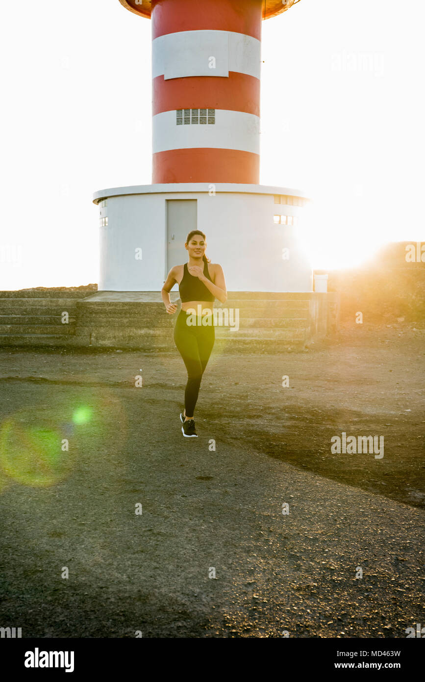 Young female runner running on coastal dirt track at sunset Stock Photo