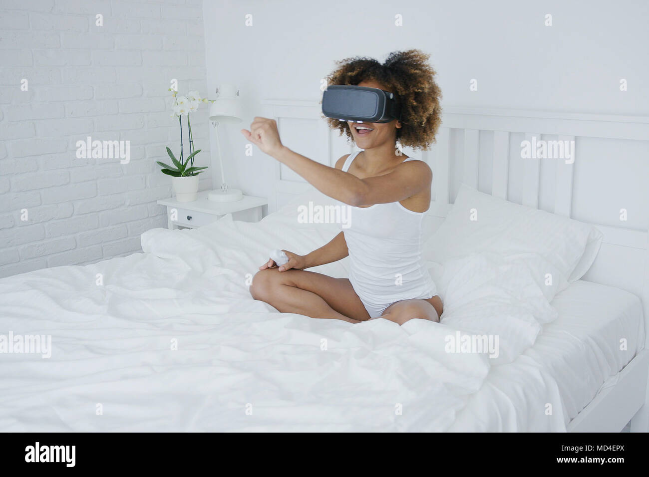 Content woman in VR glasses on bed Stock Photo