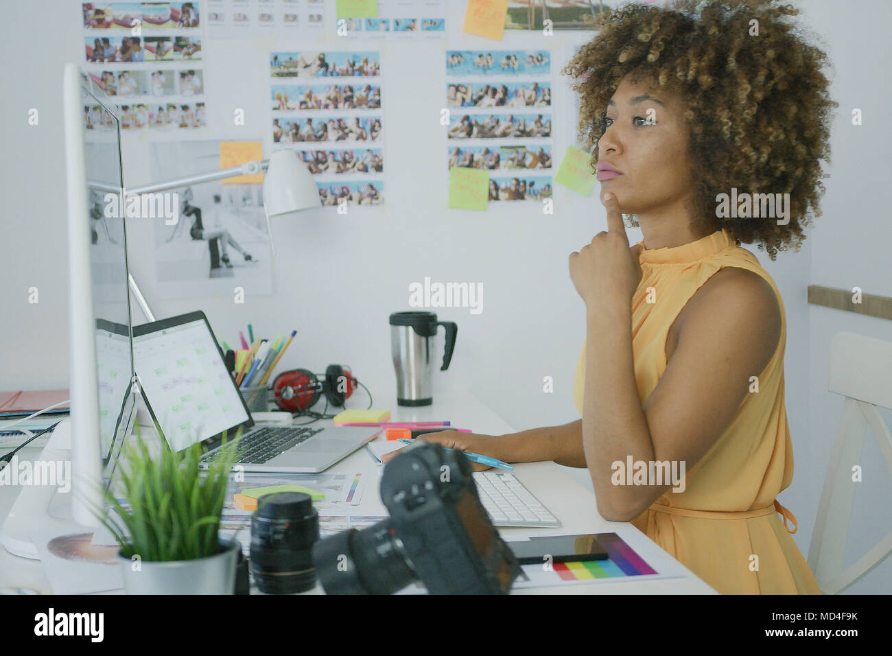 Stylish pensive worker at desktop - Stock Image